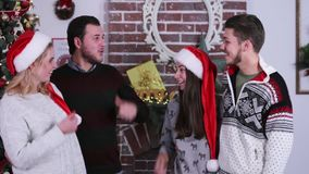 Two cute couple talking and smiling each other, show tumbs up on Christmas tree and fireplace backround. Company of friends in winter sweaters and red hats stock video