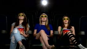 Company of girl watching a movie at cinema: horror