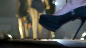 Company of girls in black shoes with travel suitcase at stylish show. In unfocused background stock video