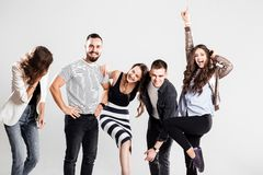 Company of girls and guys dressed in stylish casual clothes are fooling around on a white background in the studio royalty free stock photography