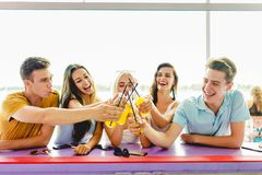 A company of good-looking friends laughing, drinking yellow cocktails and socialising at the bar in the nice summer cafe stock photography