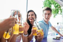 A company of good-looking friends laughing, drinking yellow cocktails and socialising at the bar in the nice summer cafe royalty free stock photo