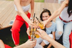 A company of good-looking friends laughing, drinking yellow cocktails and socialising while sitting on the bench and red royalty free stock images