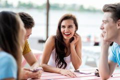 A company of good-looking friends is laughing and sitting at the table in the nice summer cafe. Entertainment, having royalty free stock image