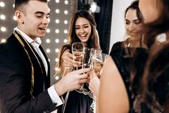 Company of happy friends dressed in stylish elegant clothes stand together and clink glasses with champagne. Party time stock photo