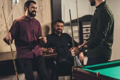 Company of happy men with drinks and cues at billiard. Bar royalty free stock images