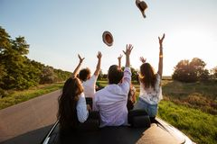 Company of happy young girls and guys sit in a black cabriolet road and throw up their hats on a sunny day. stock photo