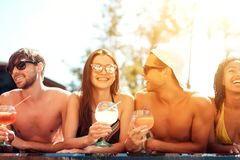 Company of joyful friends drinks cocktail drinks in pool at summertime. Swimming pool party. Multiethnic company of friends in swimming pool Royalty Free Stock Photography
