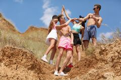A group of smiling young people gives five each other on a top of a valley on a natural blurred background. Stock Photo