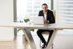 Company leader working on computer at workplace. Successful entrepreneur sitting at modern work desk in front of laptop and looking in camera with smile. Company Stock Photo