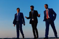 Company leaders take a walk on sunset sky background. Businessmen with confident faces in formal suits. Business, confidence and teamwork concept. Board of royalty free stock image