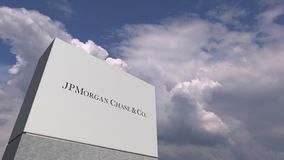 Logo of JPMORGAN CHASE on a stand against cloudy sky, editorial animation