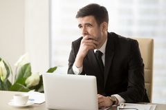 Company manager feeling sleepy at workplace. Tired businessman covering his mouth with hand when yawning at desk in office. Office worker feeling lack of sleep royalty free stock images