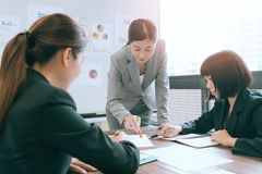 Company manager woman meeting with employees. Company manager women meeting with employees in office and pointing document content to discuss planning together stock images