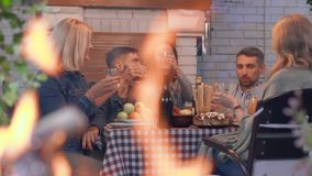 Company of people drinking alcohol and smiling sitting at the table in the background. Flame burning in the foreground. Friendly family celebrating holiday stock video