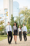 Company People. Group of young business people, formally dressed, walking through a park near their company Royalty Free Stock Images