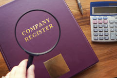 Company Register under magnifying glass Stock Photos