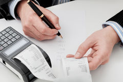 Company's finances. An accountant going through company's finances summing up the expenses Stock Images