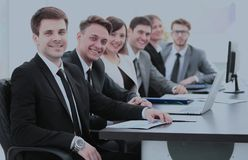 Company`s shareholders at the meeting sitting behind a Desk with Stock Photo
