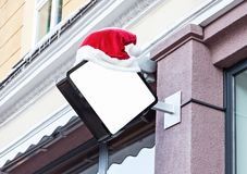 Company signage decorated with Santa hat during Christmas. White blank outdoor company signage mockup decorated with red Santa Claus hat during Christmas Stock Photo
