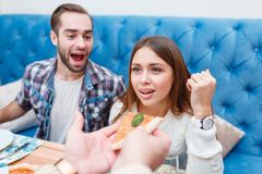 The company is sitting in a cafe, someone gives the girl a pizza, the guy in the background laughs. A company of young European people are resting in a cafe Royalty Free Stock Photography