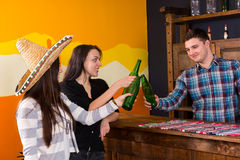 A company of smiling young people clinking bottles of beer while. Standing on the bar of Mexican bar stock images