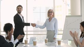 Company staff applauding while director greeting handshakes with new employee. In modern boardroom gathered multi-ethnic business people, company staff sitting stock video footage