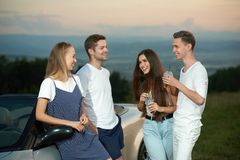 Company standing near cabriolet, smiling and communicating. royalty free stock image