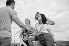 Company stylish young people spend leisure outdoors sky background. Couple meet cheerful friends with bicycle during. Walk. Cycling modernity and national royalty free stock photography