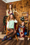 The company of three cheerful girls in a room with Christmas dec stock photos