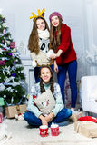 Company  of  three fanny girls near the Christmas tree in a whit Royalty Free Stock Photography