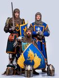 Company of three knights with helmets on a ground Stock Photos