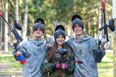 Company of three smiling paintball players posing outdoors Royalty Free Stock Images