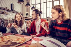 Company of three young musicians eating yummy pizza for lunch. Pizza for lunch. Company of three young active musicians eating yummy pizza for lunch stock photos