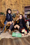 Company of two girls with gifts in the room with wooden walls. stock image