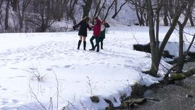 The company walks by the river in the winter. admiring the nature stock video