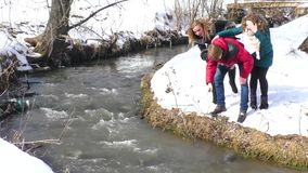 The company walks by the river in the winter. admiring the nature stock footage