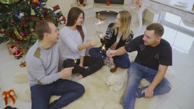 Company of young friends sit on the fluffy carpet and light sparklers. Two girls and two boys sit on the fluffy carpet and light sparklers. Christmas tree is stock video