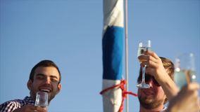 A young company of friends celebrating a birthday on a yacht during the day stock video