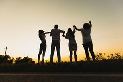 Company of young girls and guys are standing on the grass near the road on a summer day and holding their hands. royalty free stock photography