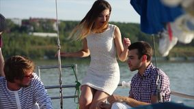 A company of friends sail on the sea on a yacht in order to relax in the summer. A company of young happy friends sail on a yacht on a summer day, friends share stock footage