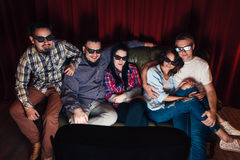 Company of young happy people watch tv at home. Company of five young happy people in 3d glasses watch tv at home. Special effects, new technologies, exciting Stock Image