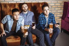The company of young men drink beer and watch TV stock photography