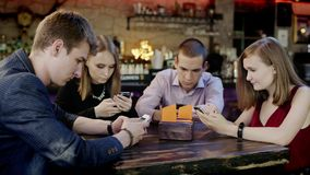 Company of young people is looking at their cellphones in the bar