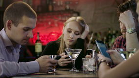 Company of young people is looking at their cellphones in the bar stock video