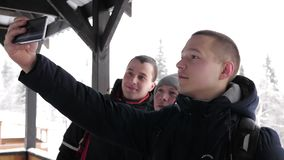 Three young tourists make selfie in the mountains in winter. A company of young tourists takes a selfie on a mobile phone in a natural park in winter. Slow stock footage