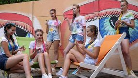 Company of youth with bright braids playing of spinners outdoors, stylish girls showing trick with fidget spinners stock video