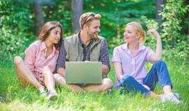 Company youth spend leisure outdoors with laptop. Friends working with laptop at green meadow. Freelance opportunity stock photo
