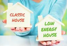 Comparação do conceito entre a casa normal e a baixa casa do consumo fotografia de stock royalty free