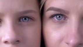 Comparación de la edad, ojos de la madre caucásica e hija al lado de otra que mira junto la cámara almacen de video